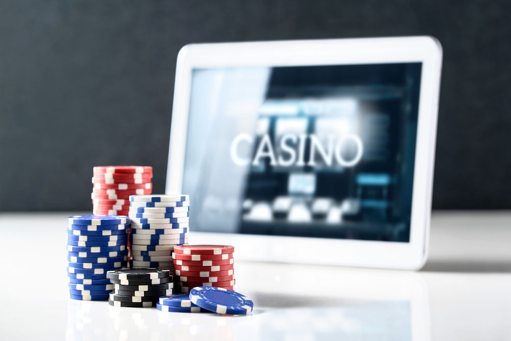 Stack of poker chips and tablet with slot machine on screen
