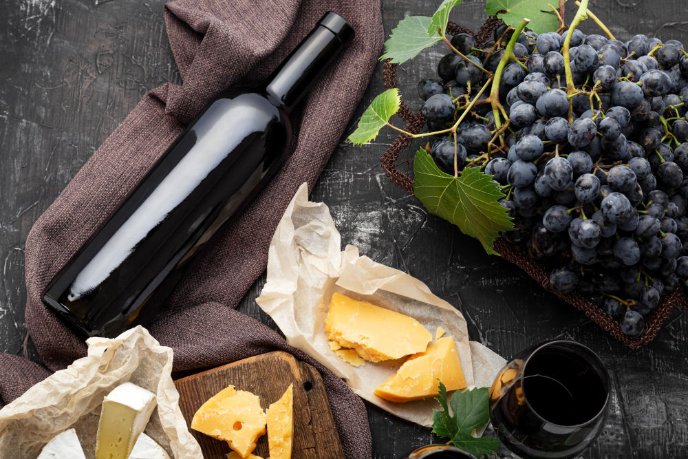 Red wine bottle different cheeses grapes