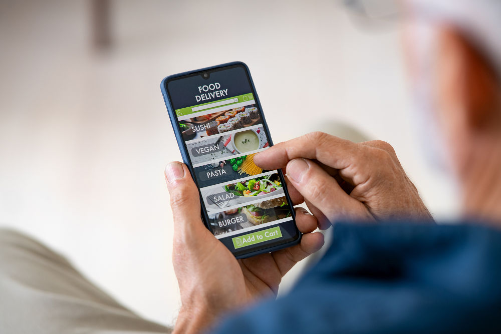 Man holding smartphone while ordering a food delivery at home