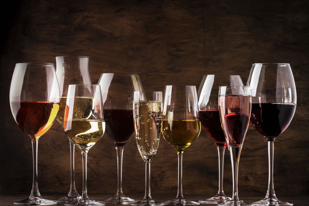 Red, white wine, rose and champagne in wine glasses on vintage wooden table background