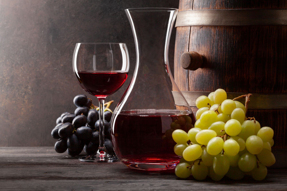 Wine decanter, glass of red wine and old wooden barrel.