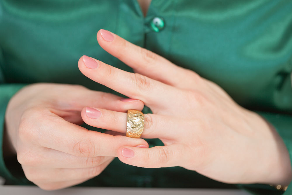woman tries on a large gold ring on his finger