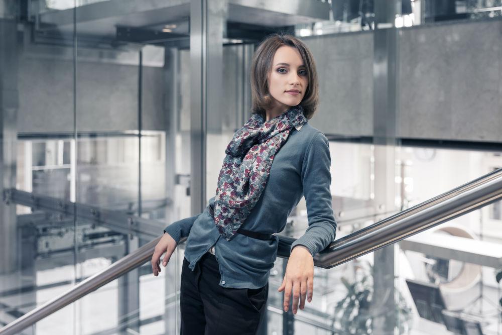 Stylish female model in blue cardigan and silk scarf