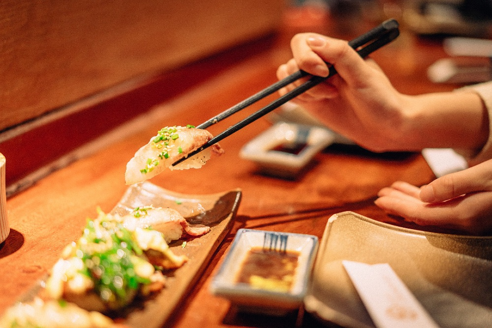 Woman eating sushi in a restaurant
