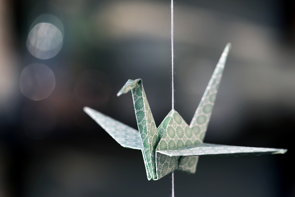 An origami swan hanging from a piece of string