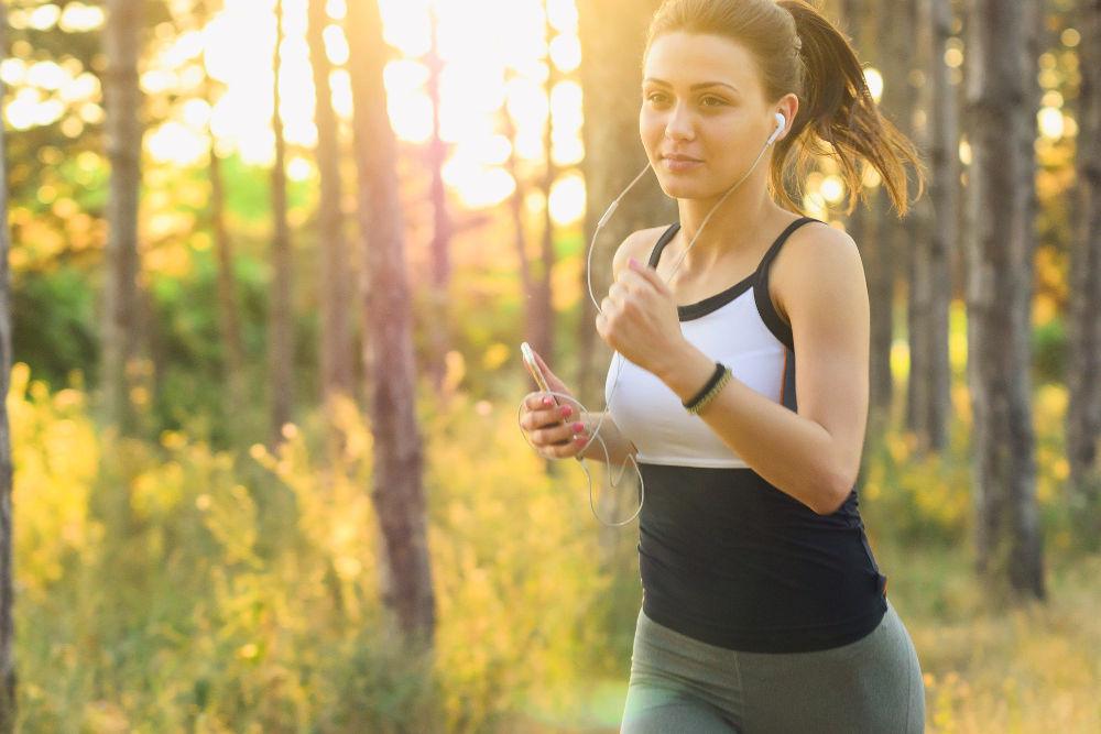 Woman running through woodlands