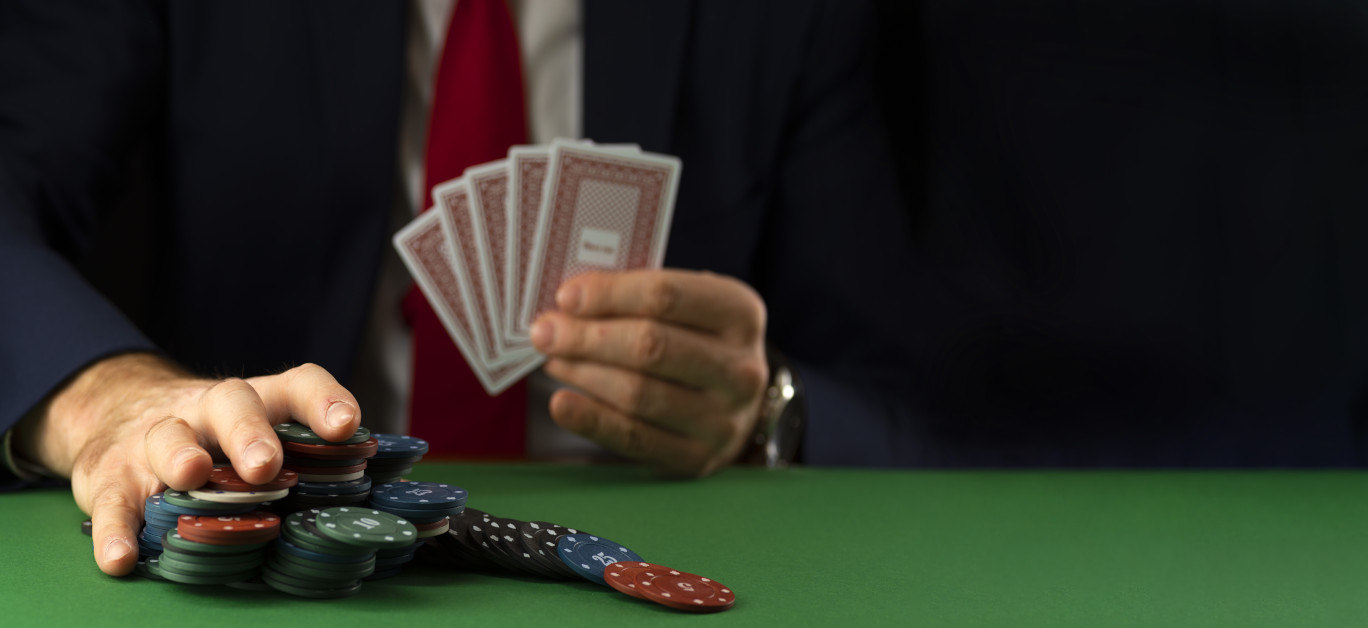 Businessman At Green Playing Table With Gambling Chips And Cards