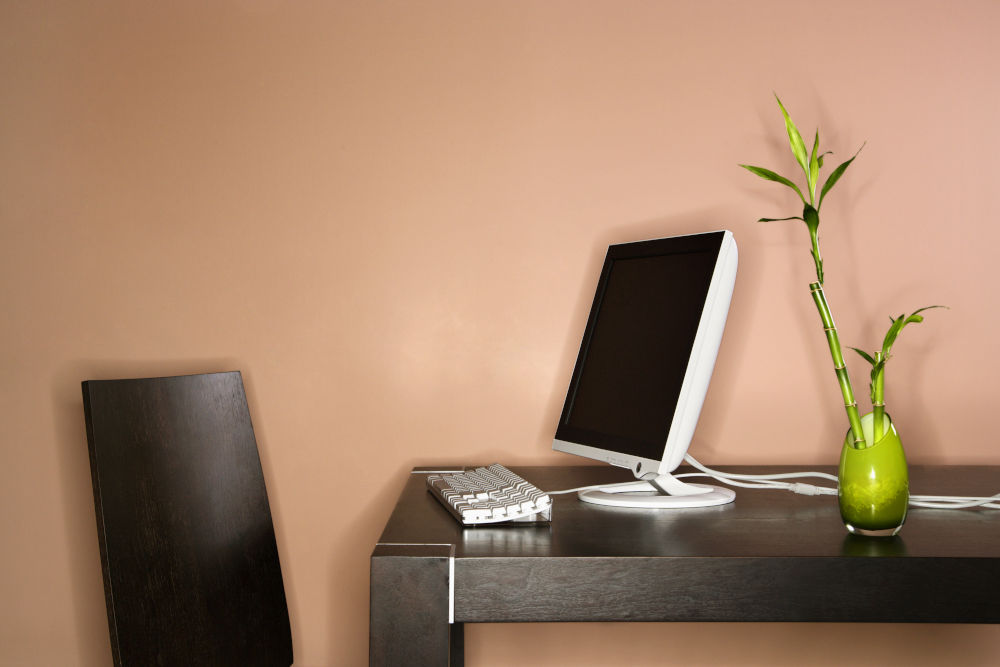 Computer on a table sitting next to a bamboo plant in a vase.