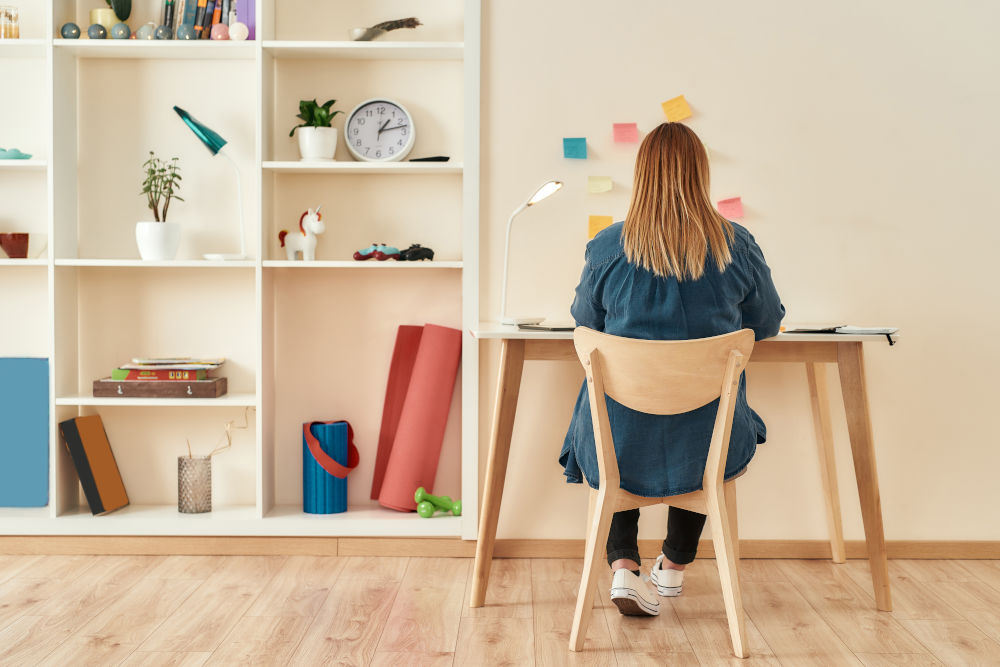 Young woman in casual clothes sitting at office desk