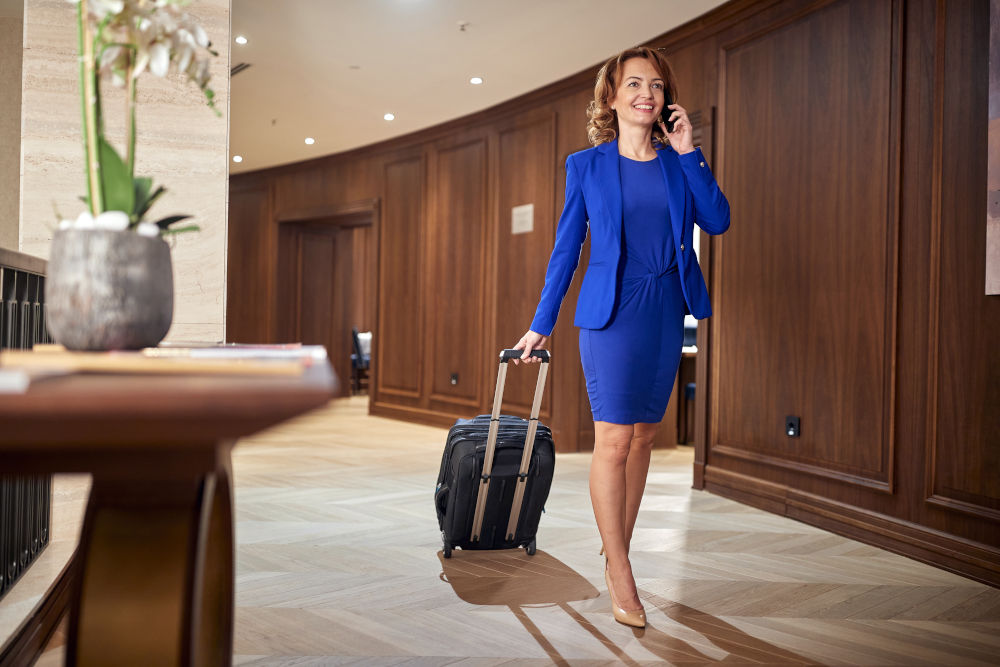 businesswoman entering hotel on her trip, with her suitcase