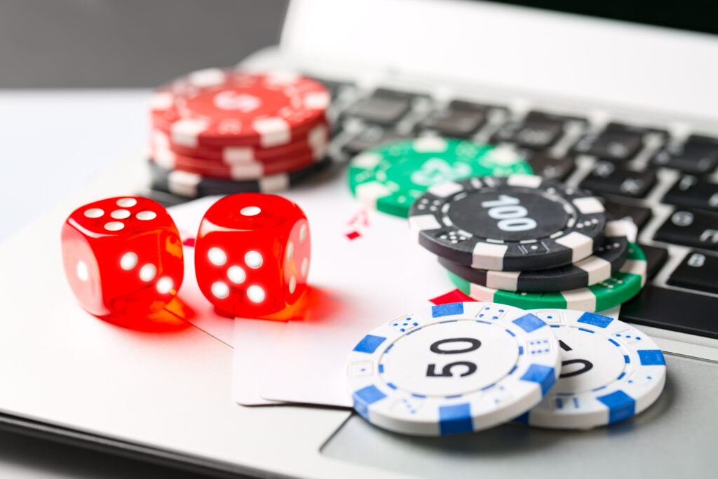 Gambling chips with dice and playing cards on laptop