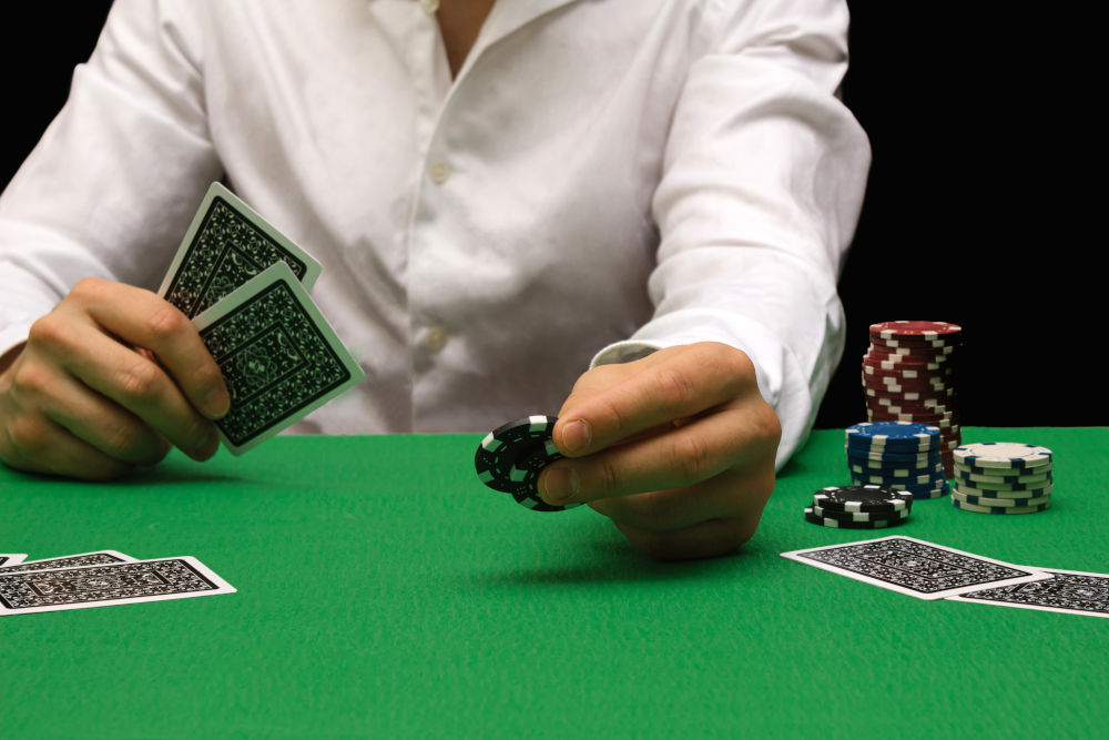 Person in a night casino playing poker, gambling money with chips