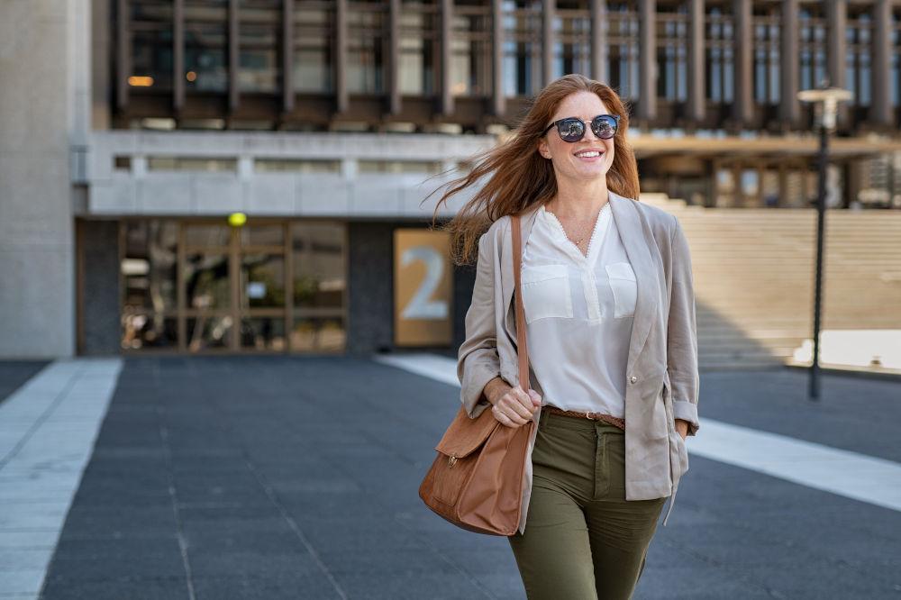 woman wearing sunglasses and walking on street
