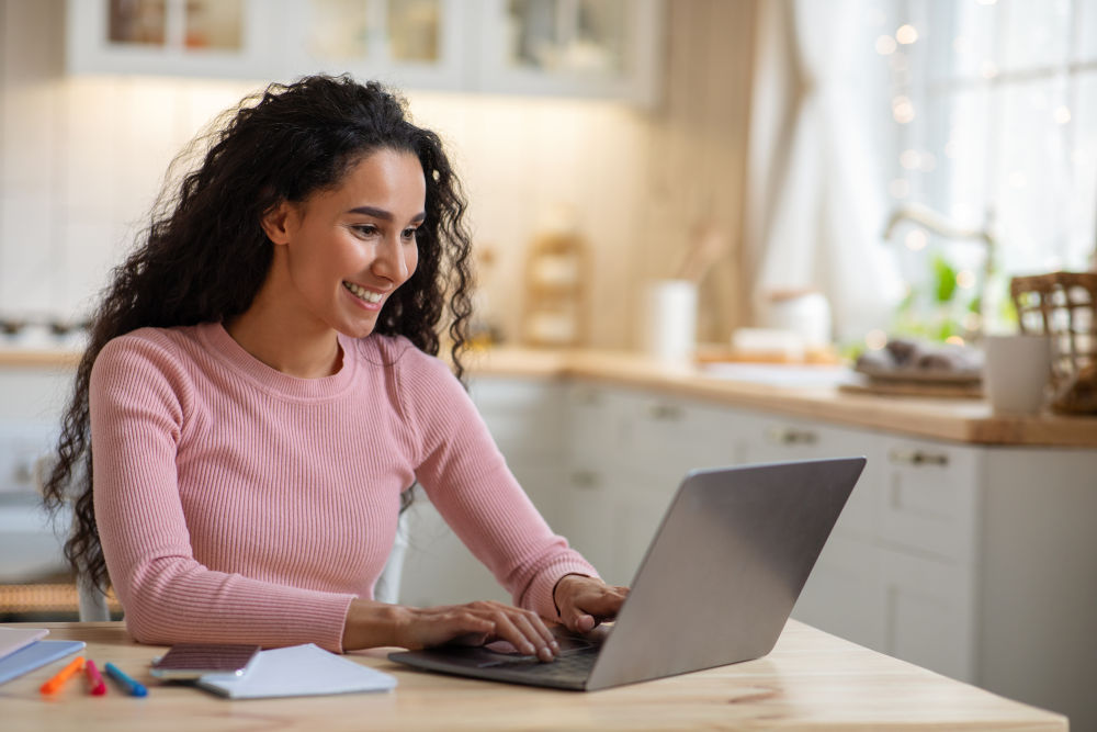 Young Freelancer Lady Working With Laptop In Kitchen