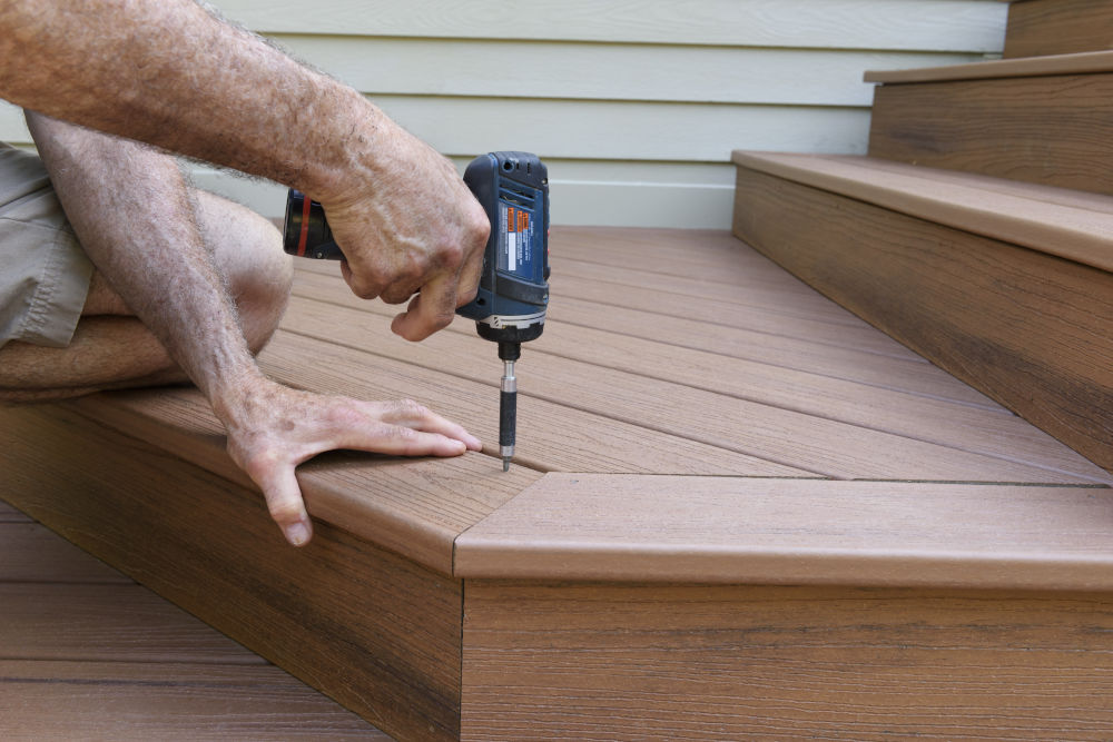 Worker Installing Composite Wood Decking on Porch Steps