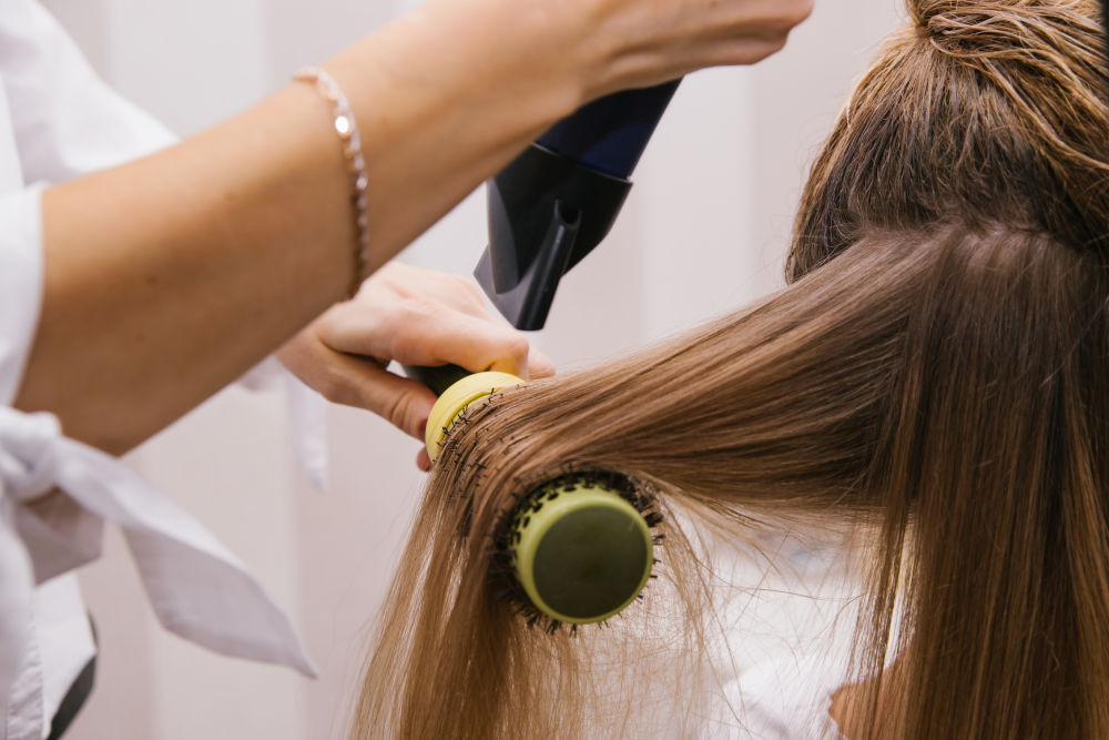 young woman dries her hair with a hair dryer