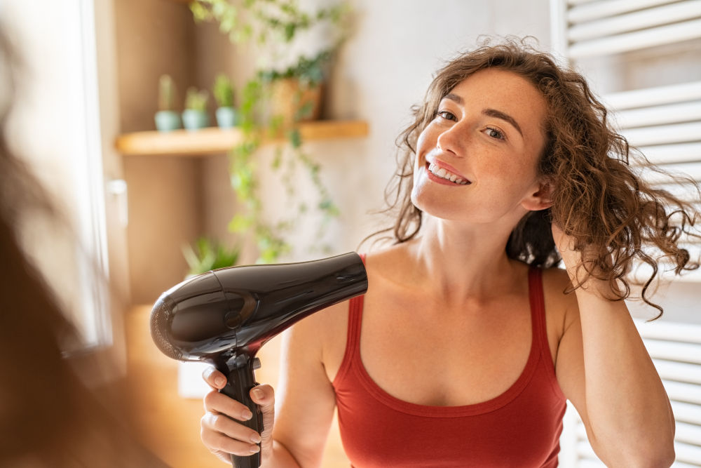 Girl using a hair dryer and smiling
