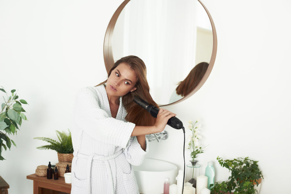 woman drying using hair dryer near mirror
