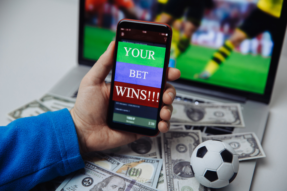 Lucky winner at football betting with phone in hand and dollar bills