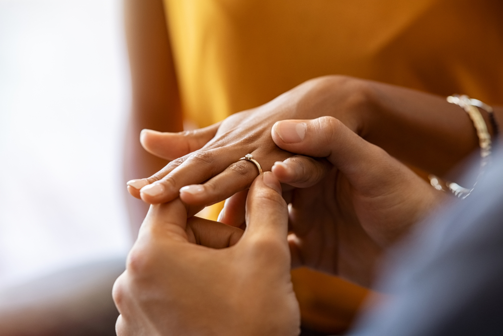 Close up of man putting engagement ring on his girlfriend