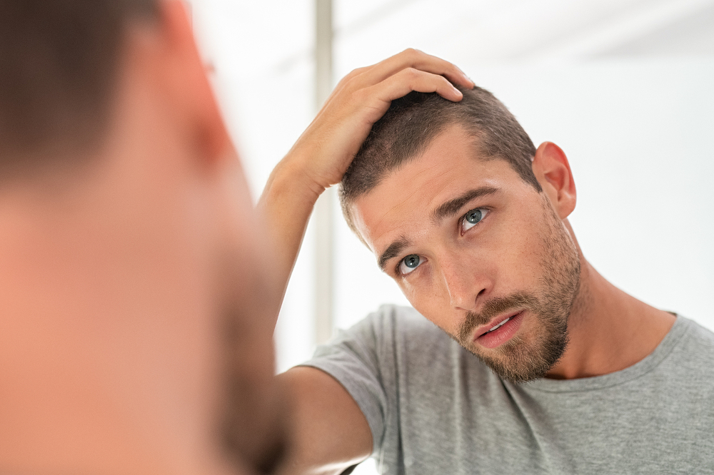 man looking at mirror in bathroom at home.