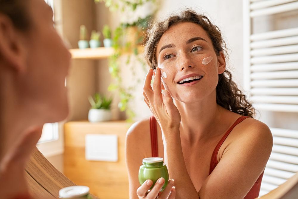 Woman putting on skincare