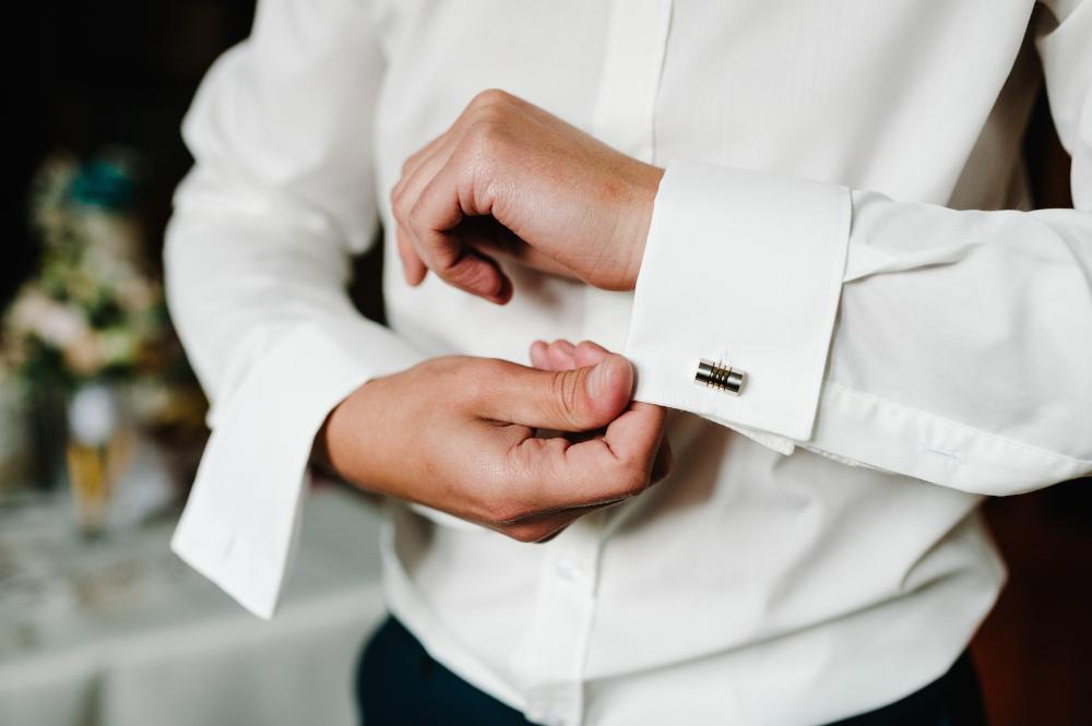 man buttoning cufflinks