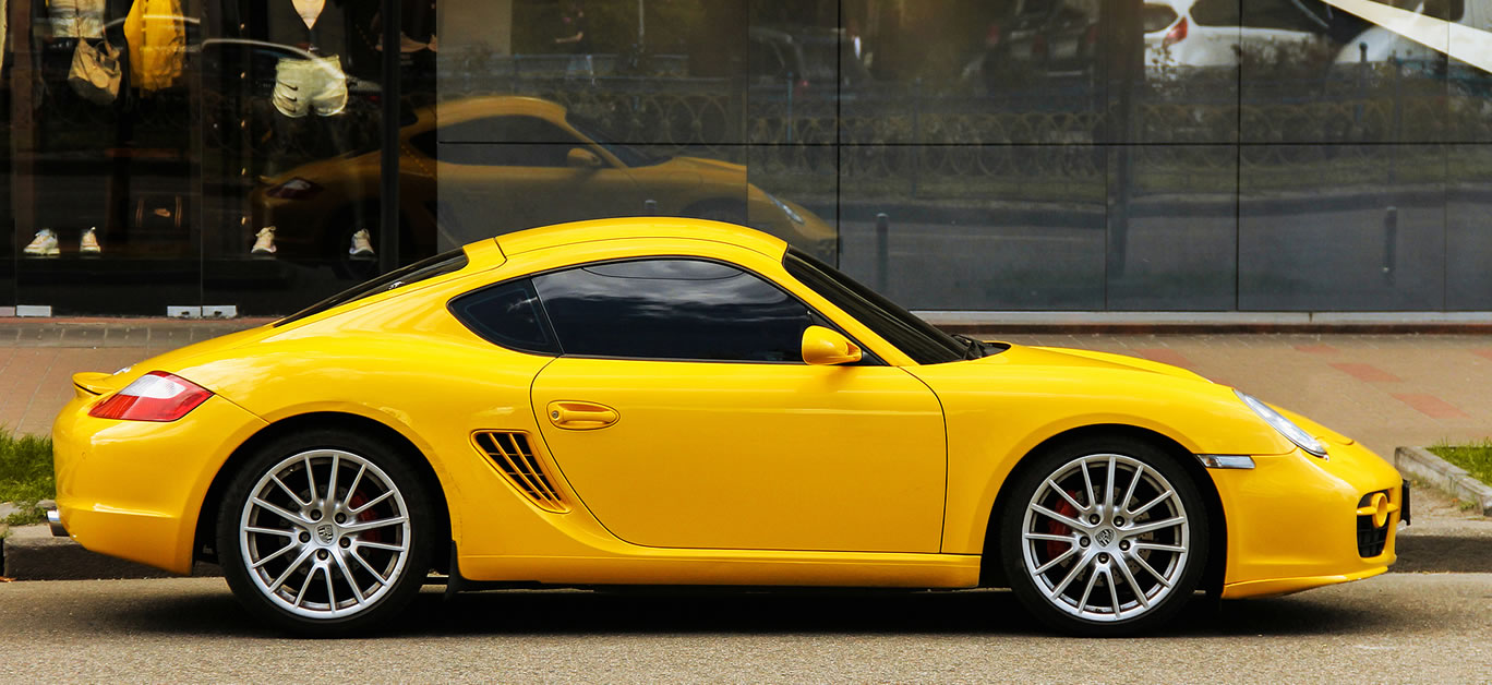 Yellow supercar Porsche Cayman s parked in the city