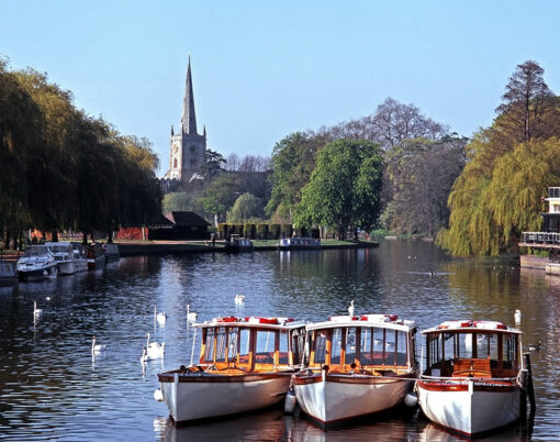River Avon with pleasure boats moored and Church to rear Stratford-upon-Avon Warwickshire England UK Western Europe.