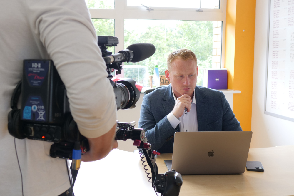 Adam Stott being filmed in office