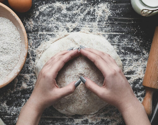 Beat flour and kitchen utensils, a baking dish, a rolling pin with eggs on the table