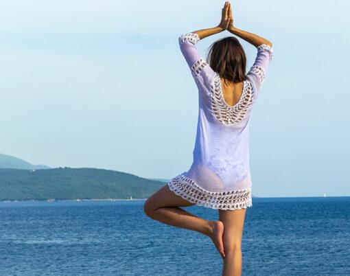 Girl doing yoga on tropical beach
