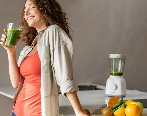 Happy young woman standing in kitchen and holding glass of detox juice