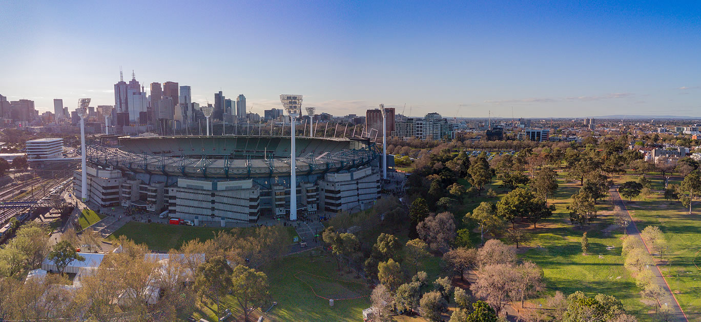 Aerial shot of the Melbourne Cricket Ground with Melbourne city skyline and late afternoon sun behind