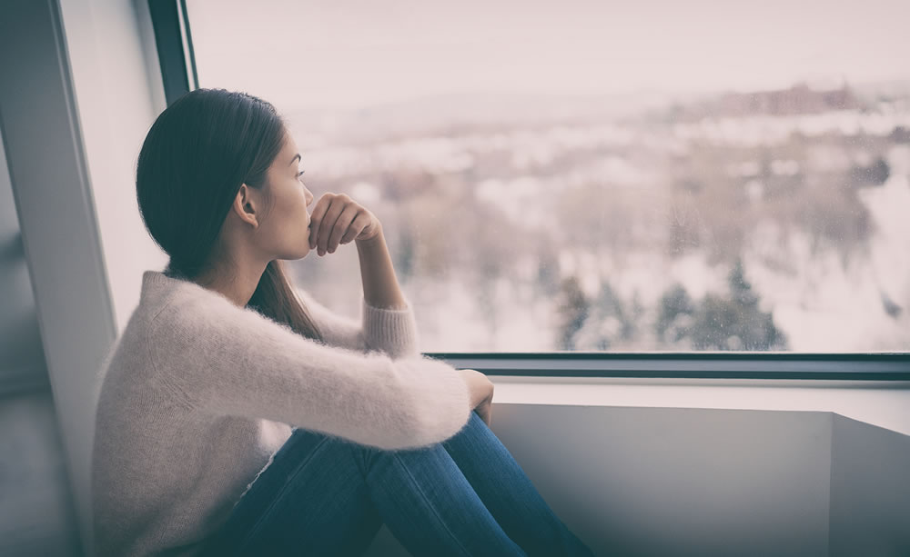 worried woman looking out the window