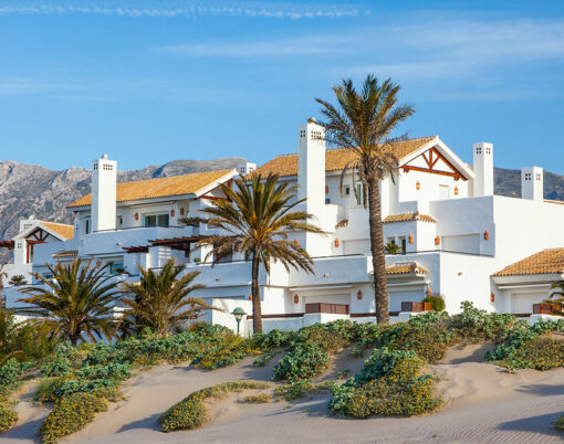 A luxury Apartment and Villa development on the beach i on the Costa del Sol near Marbella. Spain with beautiful deep blue sky and mountains in the background
