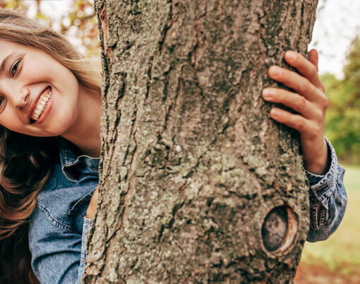 happy woman behind a tree