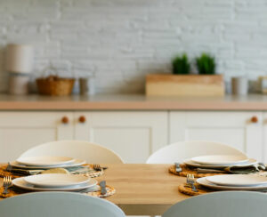 White plates with stainless steel spoons and forks on the plate mats on wooden table